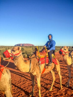 Matt riding a camel at Uluru