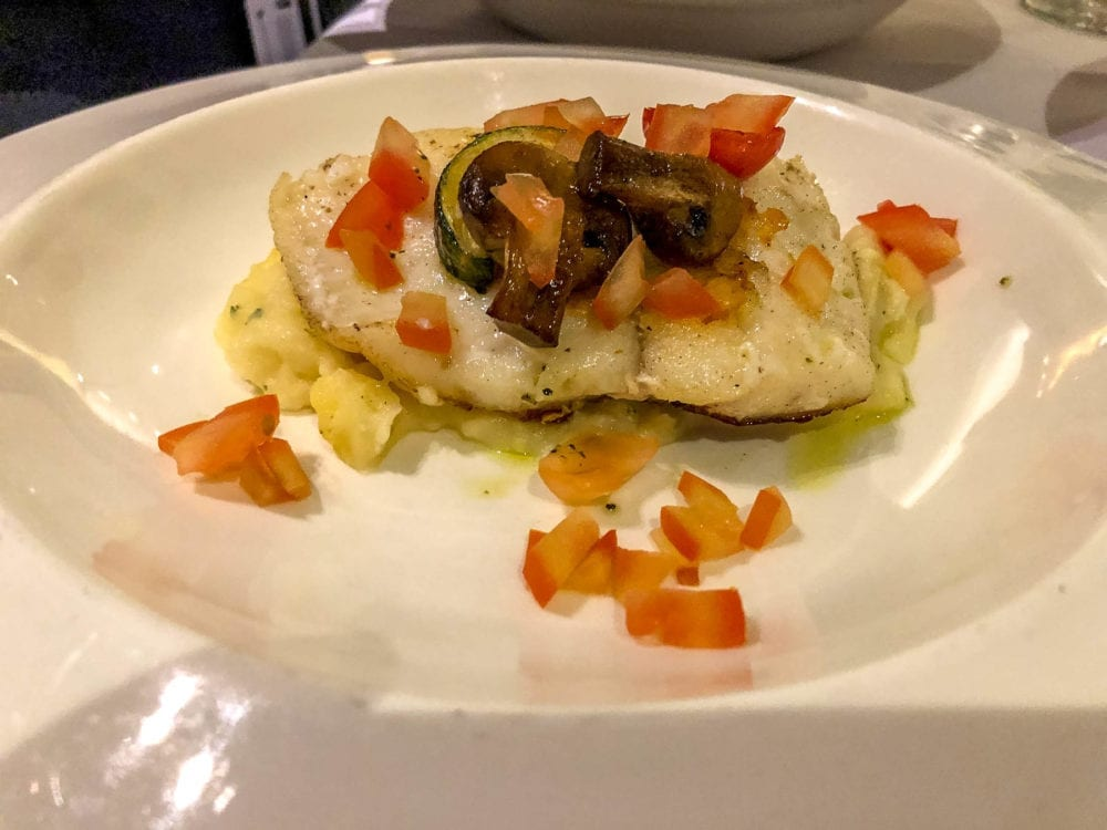 Angelo's Secondi Filetto di Merluzzo Spadellato. Pan-seared cod fillet  with potato puree, mushrooms, roast zucchini and cherry tomatoes.